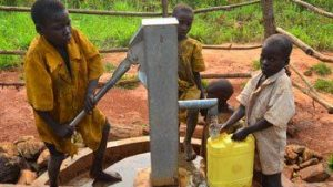 African children hand pumping water from a well