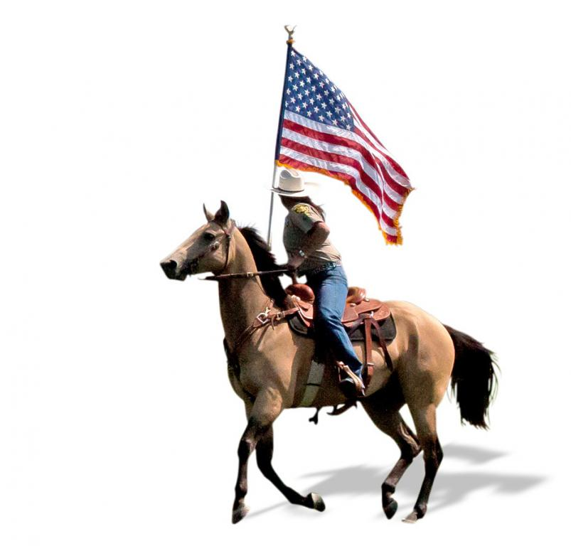 man carrying an American flag riding a horse