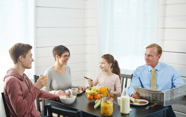 Happy family eating at breakfast table